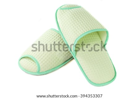 A pair of green slippers on a white background.