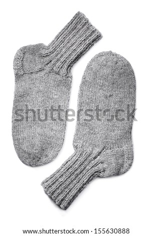 A Pair of hand-knit grey wool socks on white background with natural shadows.