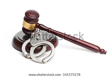 A pair of handcuffs and gavel - stock photo