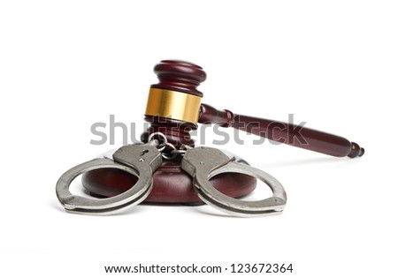 A pair of handcuffs and gavel are isolated for legal concepts. - stock photo