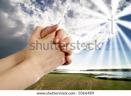 A pair of hands in a praying position set against a beautiful prairie lake landscape with a cross in the sky on the right side. - stock photo
