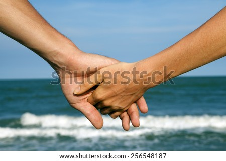 a pair of hands that hold each other against the backdrop of the sea. Holiday, love, family, travel