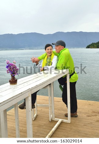A pair of happy lovers embrace the by the lake - stock photo