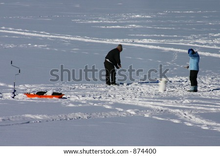 A pair of ice fishermen on a frozen lake - stock photo