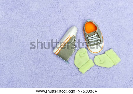 A pair of infant baby shoes and socks on a fluffy purple blanket. - stock photo