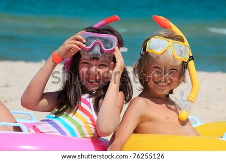 A pair of kids sitting on the beach. - stock photo