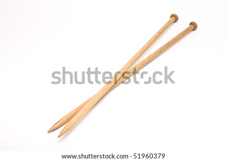 A pair of large wooden knitting needles from low perspective isolated against white background.