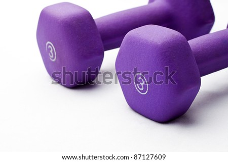 A pair of 3 lb purple neoprene weights beside each other on a white surface - stock photo