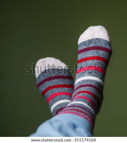 a pair of legs with striped socks on against a green wall - stock photo