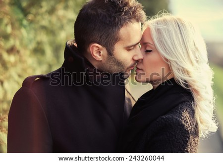 a pair of lovers kissing on a warm spring day in the park - stock photo