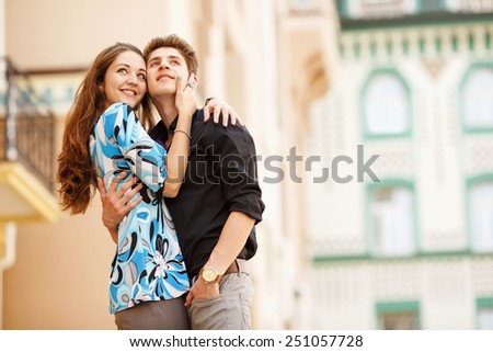 A pair of lovers people on the city walk. The love story of two young people. Man and woman embracing each other. Walking through the city summer day. Feelings of love between two people. Love story. - stock photo