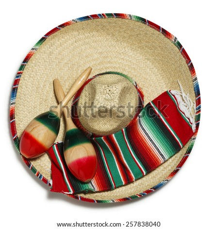 A pair of maracas and a colorful Mexican blanket on a sombrero on a white background - stock photo