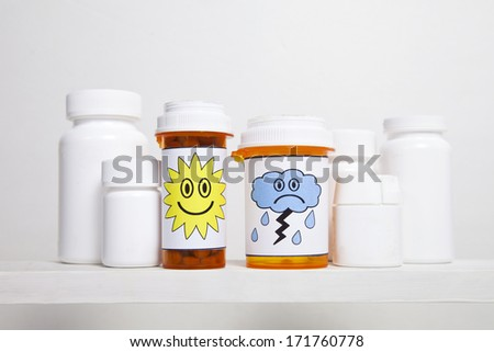 A pair of medicine bottle with a smiley face and frowny cloud on the labels sit on a shelf with other pill bottles. - stock photo