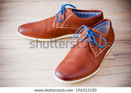 A pair of men's leather shoes with colorful laces placed on wooden floor - stock photo