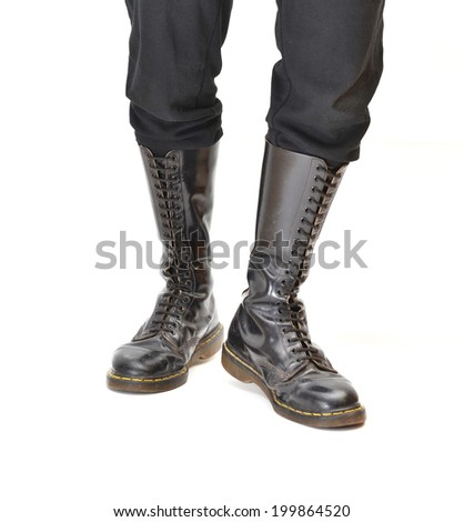 A pair of old and rugged men's/unisex knee-high black 20-eyelet lace-up combat boots - stock photo