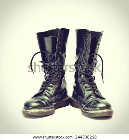 A pair of old and rugged men's/unisex mid-calf black 14 eyelet lace-up combat/ranger boots - vintage processes - stock photo