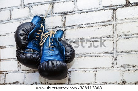 A pair of old blue and black boxing gloves hanging on white brick wall background. - stock photo
