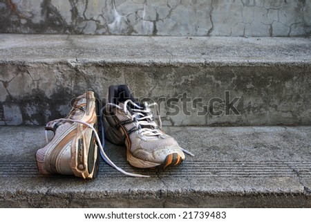 A pair of old used  running shoes on cement steps. - stock photo