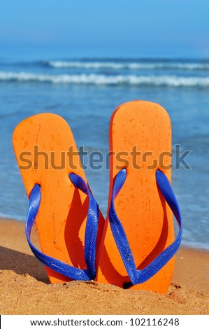 a pair of orange flip-flops on the sand of a beach - stock photo