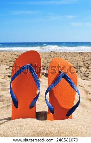 a pair of orange flip-flops on the sand of a beach
