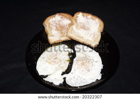 A pair of over easy eggs with a side of toast - stock photo