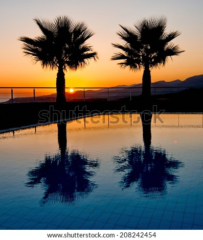 A pair of palm silhouettes reflecting in a pool on a summer vacation.  The sun is rising in the background over the Cretan mountains in Malia, Crete near Heraklion, Greece - stock photo