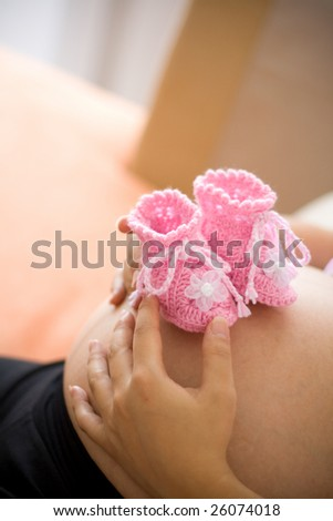 A pair of pink color baby booties on pregnant motherâ??s belly. This picture was taken at home, 3 weeks before due date. Natural lighting. - stock photo