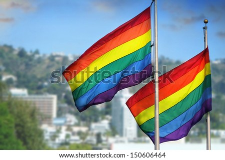 A pair of rainbow flags waving in wind against city background of West Hollywood, California - stock photo