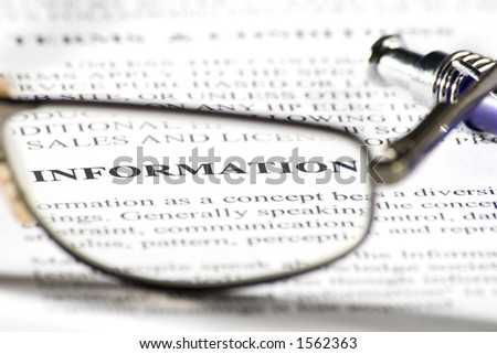 A pair of reading glasses on paper and the word 'information' in focus - stock photo