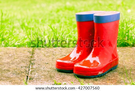 A pair of red children's wellies outside in wet weather