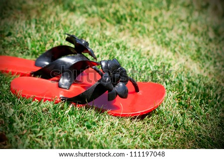 A pair of red  flip flops with flowers left on green grass