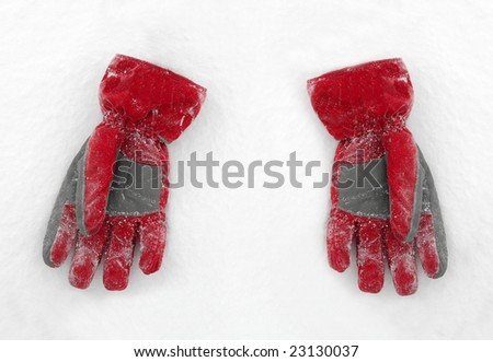 A pair of red gloves on the snow - stock photo
