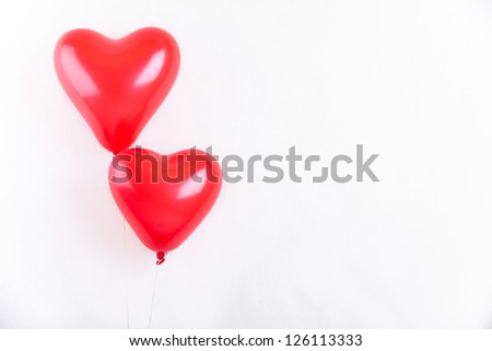 A pair of red heart shaped red balloons on white background