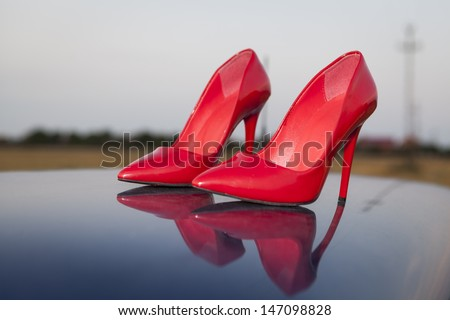 A pair of red high heel shoes on top of a blue car with reflection - stock photo