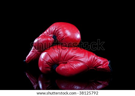 A pair of red leather boxing gloves on a black background with copy space - stock photo