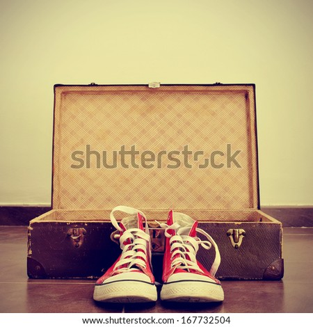 a pair of red sneakers in front of an open old brown suitcase with a retro effect - stock photo