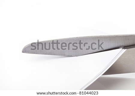 A pair of scissors  cutting a piece of paper - stock photo