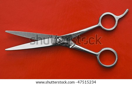 a pair of Scissors on red background - stock photo