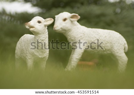 A pair of sheep and a lamb in the grass. Ceramic White plaster statuette. The plot of the lamb lovers.