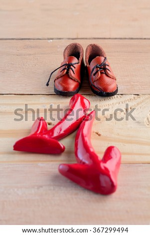 A pair of shoe standing with red arrow symbol pointing in two different directions for the concept of making decision - stock photo