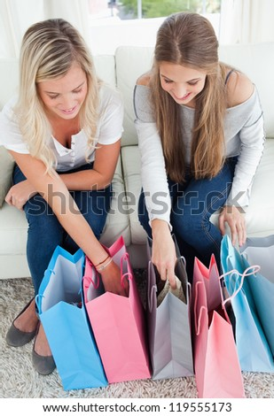 A pair of smiling girls looking into their shopping bags