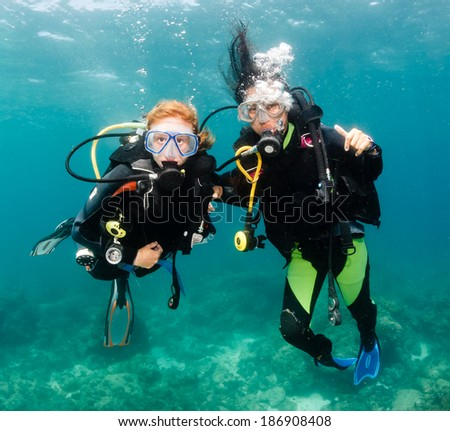 A pair of smiling, happy SCUBA divers - stock photo