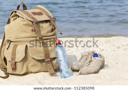 A pair of sneakers, a backpack and a bottle of water on the lake - stock photo