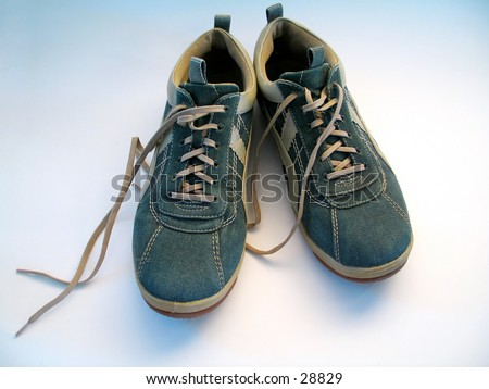 A pair of sneakers. Focus on both sneakers. Shoelaces untied. - stock photo