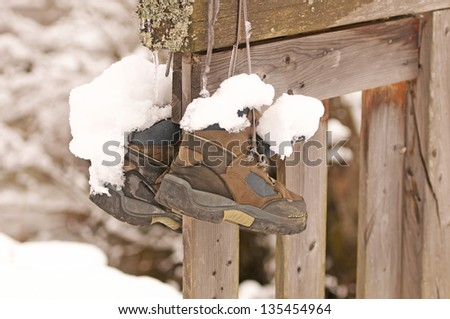 a pair of snow-covered hiking boots hanging on a wooden fence - stock photo