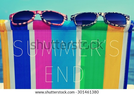 a pair of sunglasses on a colorful deck chair and the text summers end - stock photo