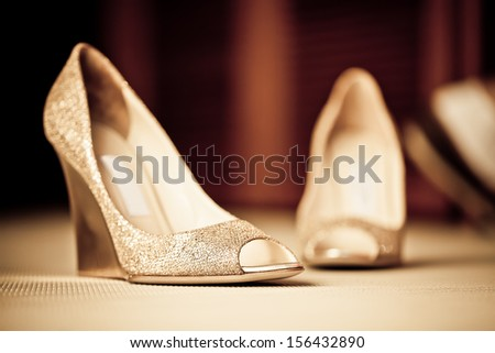 a pair of textured golden shoes on the carpeted floor - stock photo