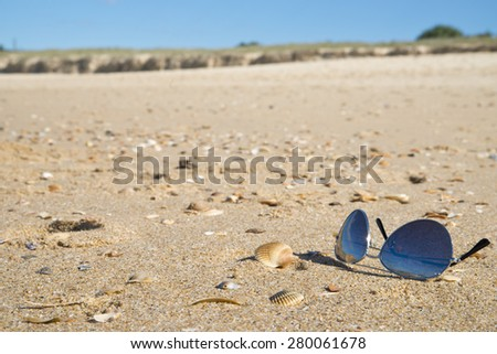 A pair of tinted sunglasses on beach sand.Shallow focus on foreground. There are some seashells scattered around the beach. Background has out of focus surf and island. Sun glare on sun-glass frame.  - stock photo