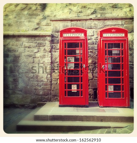 A pair of traditional British red phone boxes against the wall of Edinburgh Castle, Scotland. Cross processed to look like and aged instant photo. - stock photo