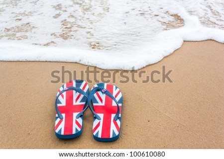 A pair of Union-jack patterned flip-flop sandals, on the beach, by the sea.